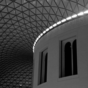 A black and white photo inside a white building with a glass roof
