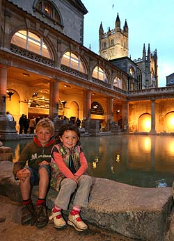 a photograph of two children sitting next to a Roman bath