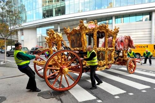 A photo showing workmen wheeling an elaborate gilded carriage across a street
