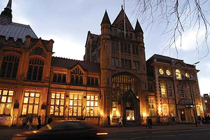 A photo of a Gothic Revival building lit up at dusk
