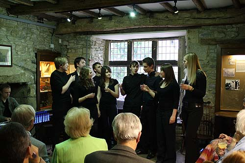A group of young people dressed in black perform for an audience in a historic room