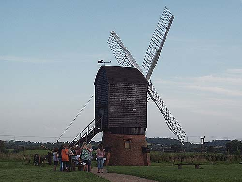 A photo of people standing outside a large wooden windmill