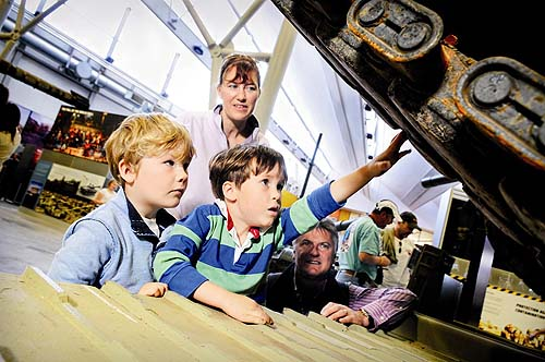 A photo of children looking underneath an armoured vehicle