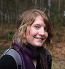 A photo of a woman in a forest smiling