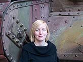 A photo of a woman smiling in front of a tank