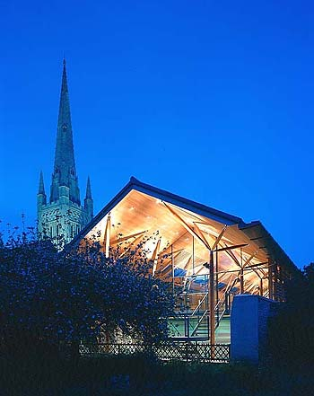 A photo of an ancient cathedral spire with a modern annex lit up at night