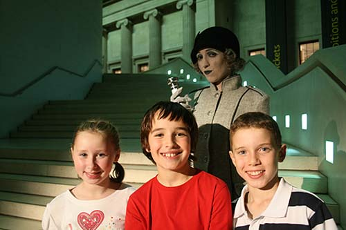 A photo of a ghostly lady in 1920s costume and smiling children in a museum