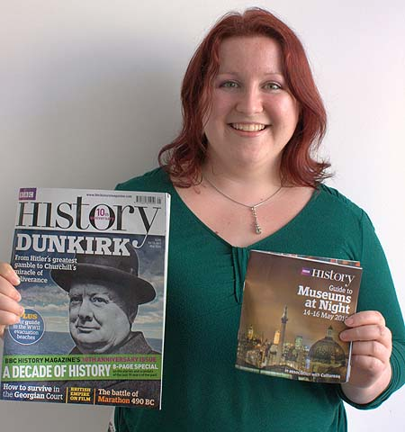 A photo of a smiling marketing co-ordinator clutching two magazines