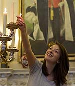 A photo of a smiling woman lighting candles