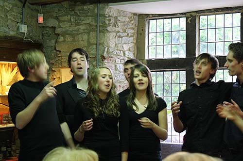 A photo of young people singing inside a historic building
