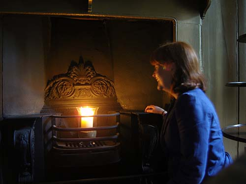A photo of a woman lighting a candle