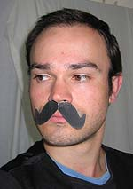 A photo of a man wearing a cardboard moustache