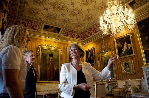 A photo of a guide pointing to a chandelier inside a historic building