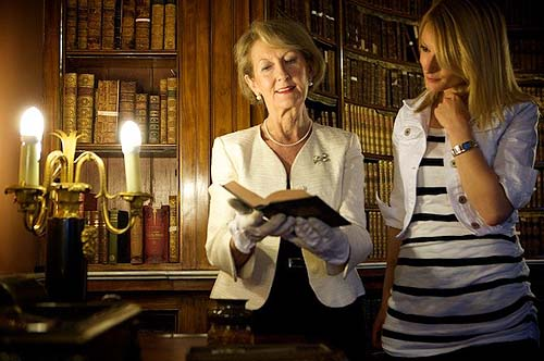 A photo of two women looking at a book in an old library