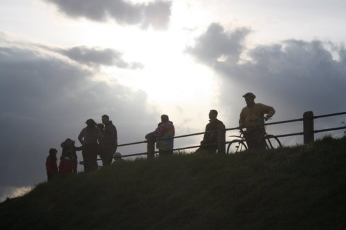 A photo of people silhouetted against a cloudy sky
