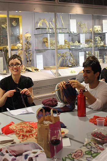 A photo of a couple knitting in a room with skeletons