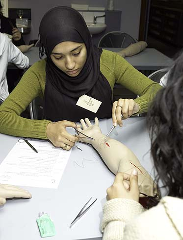 A photo of a woman carefully suturing a wound in a fake arm