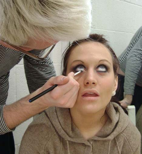 A photo of a dancer having eyeliner applied
