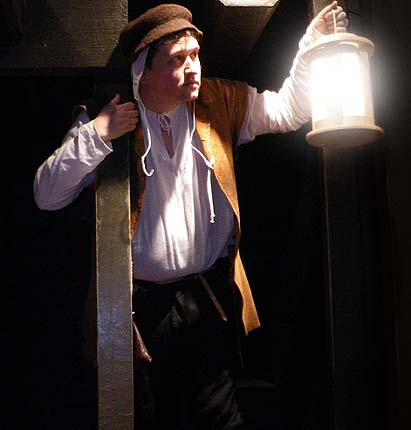 A photo of a man in Tudor costume holding a lantern