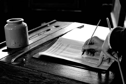 A black and white photo of somebody writing at a desk with a quill pen