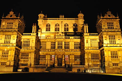 A photo of the outside of a large historic house lit up at night