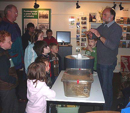 A photo of people gathered around a table looking at mice in a plastic box