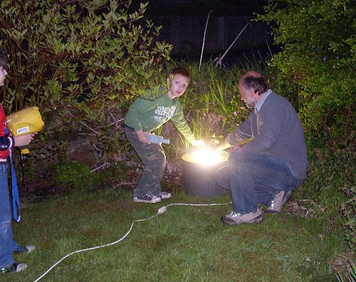 A photo of a man and children placing a bright light in a garden