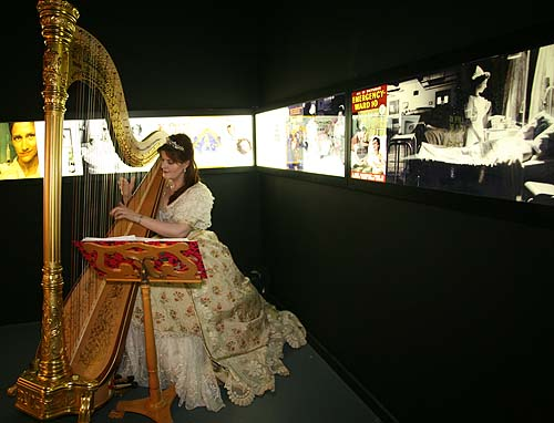 A photo of a harpist in Victorian dress performing in a museum