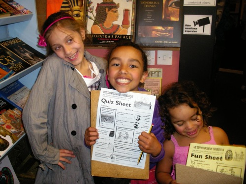A photo of smiling children with a worksheet in a museum