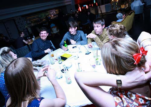 A group of smiling people around a table in a gallery at night