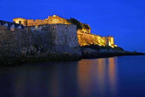 A photo of a lit-up castle reflected in the sea at night
