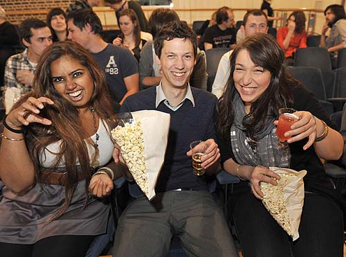 A photo of people eating popcorn and growling at the camera