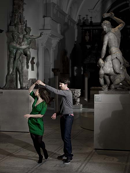 A photo of a man and a woman dancing surrounded by sculptures