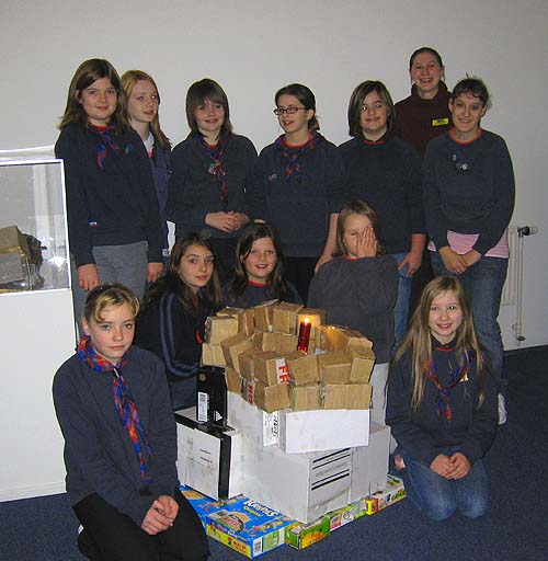 Girl Guides gathered around a cardboard model in a museum