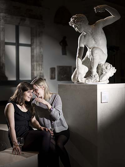 A photo of two girls drinking wine in a sculpture gallery