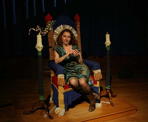 A woman seated upon a knitted throne playing with her mobile phone