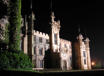 A stately home dramatically lit up at night