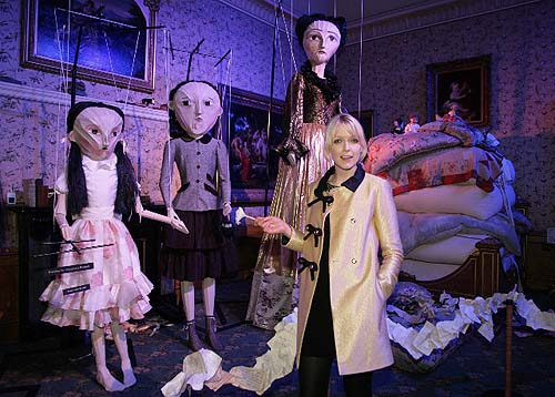 A photos of a woman in a bedroom with enormous puppets