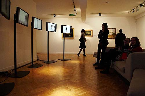 People looking at video art on screens