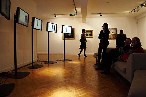 People looking at video art on screens