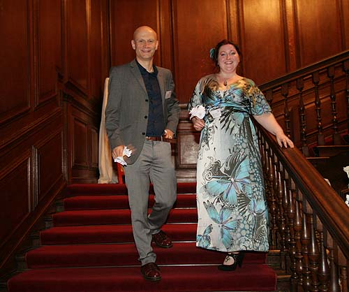 A glamorous couple descending a wood-panelled staircase