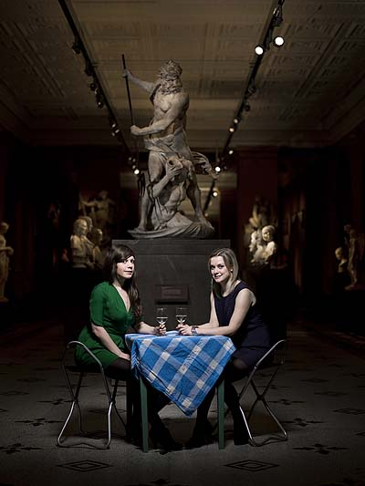 A photo of two women drinking wine at a table in a sculpture gallery