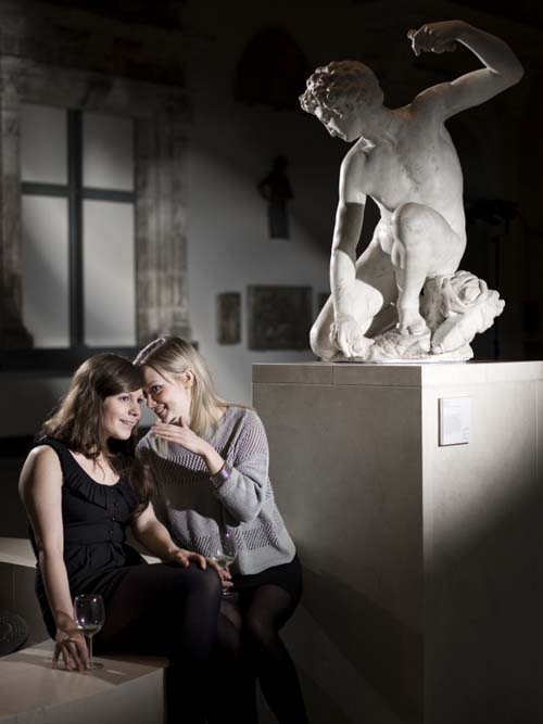 A photo of two girls drinking wine by a statue in a museum