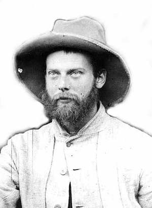A bearded Victorian man wearing a hat and a look of determination