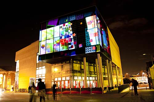 Exterior of a modern city centre building lit up at night