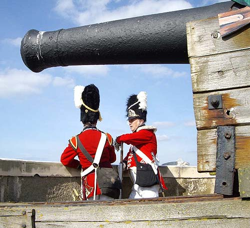 A massive cannon dwarfing two Napoleonic soldiers