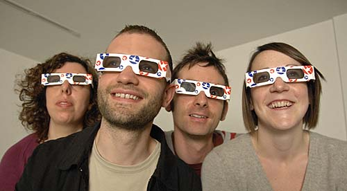 4 smiling people wearing 3D glasses