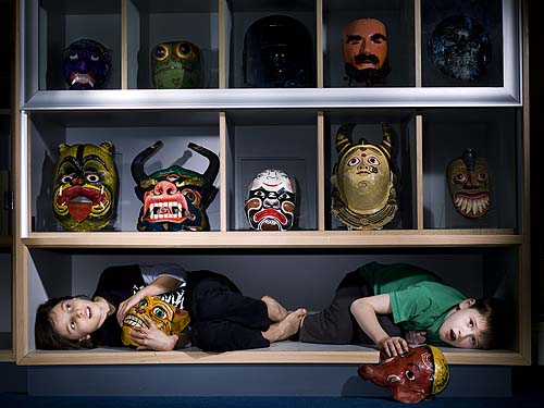 Two children clutching masks, underneath a display of masks
