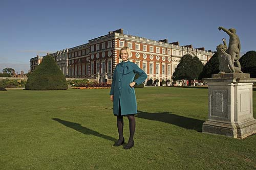 A woman in a turquoise coat standing in front of a massive historic building
