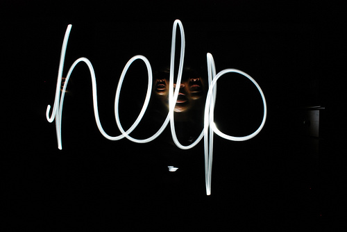 The word HELP written with a torch in the darkness